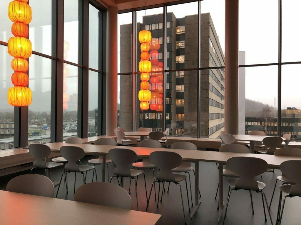 ett stort lunchrum med vackra, asien-inspirerade lampor framför de fönstren