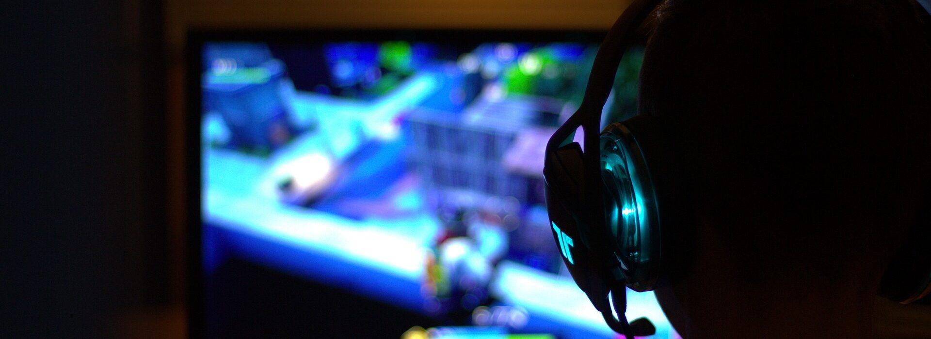 person sitter i mörkret framför datorn och spelar spelet Fortnite