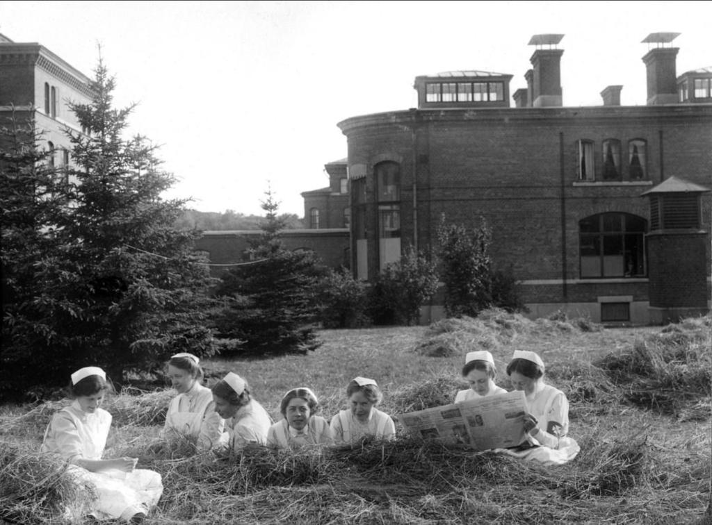 Sjuksköterskor ligger i gräset och läser tidningen, de ser ut att ha trevligt.