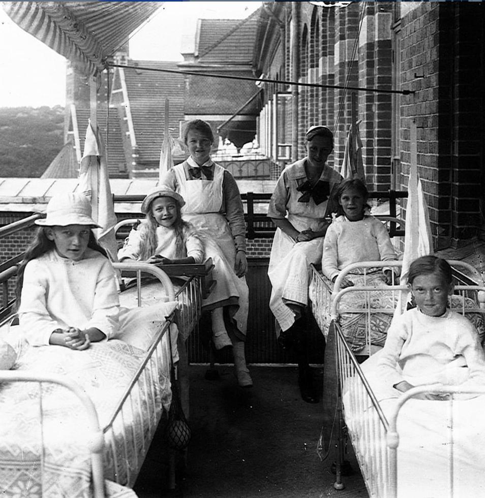 flera barn ligger i små sjuksängar på en balkong. flera har hattar på sig.
