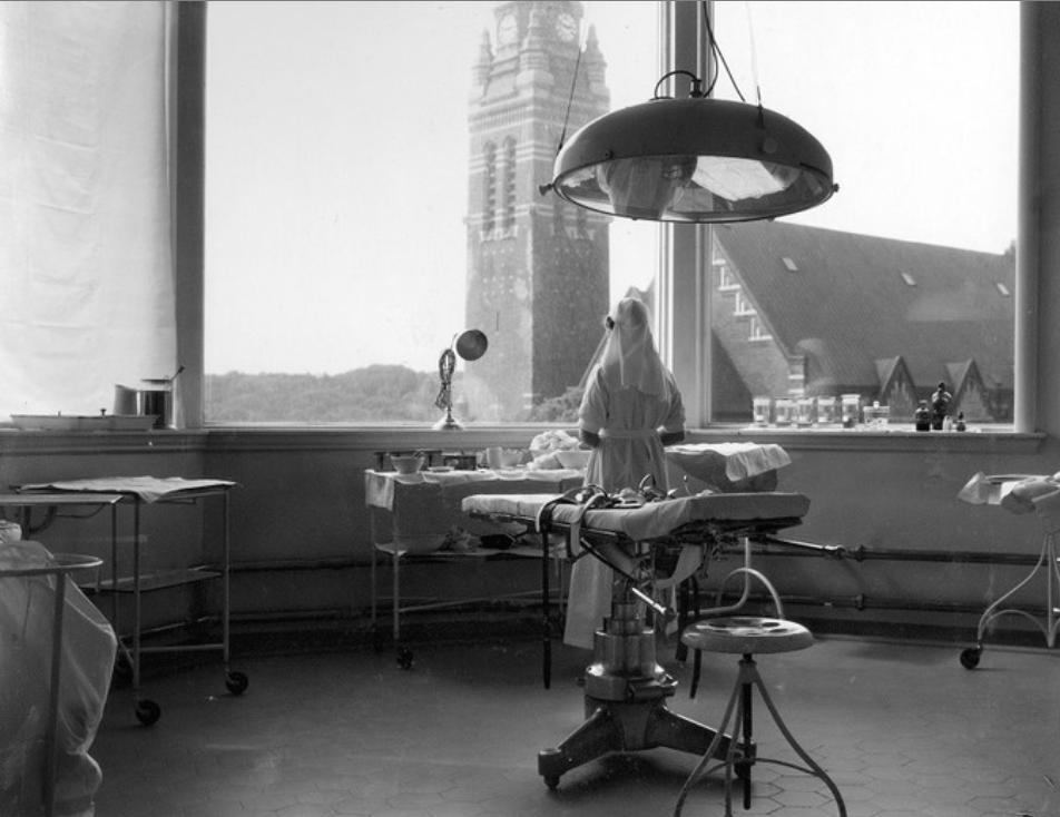 en stor sal med enorma fönster och en operationslampa mitt i. utanför fönstret tronar Annedalskyrkan.