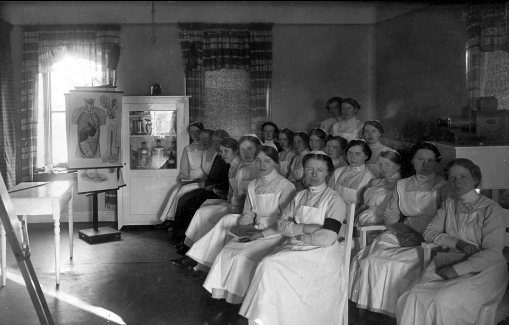 Flera sjuksköterskeelever sitter i en föreläsningssal. De har gammeldags vita dräkter bilden är tagen 1917