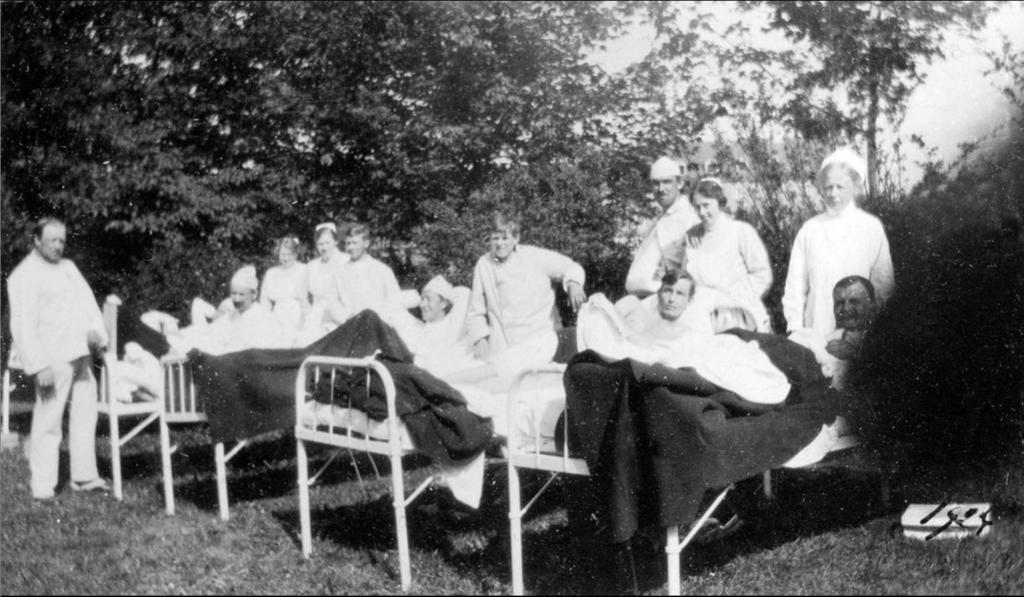 Patienternas sängar har dragits ut i en berså och här ligger patienterna i solen och ser ut att njuta tillsammans med vårdpersonalen.