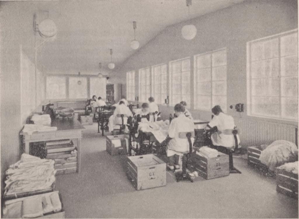 kvinnor sitter böjda över bord och syr kläder.