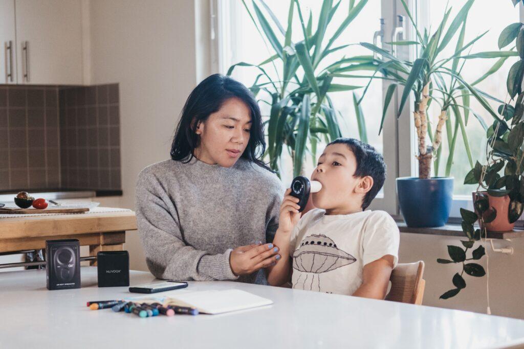 en kvinna hjälper ett barn att blåsa spirometri. barnet har som ett rör i munnen som han blåser i